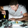 Handsome computer engineer working by night with screw driver — Stock Photo #33439303