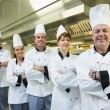 Team of chefs smiling at the camera — Stock Photo #33439399