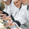 Stock Photo: Team of chefs in row garnishing dessert plates one girl smiling at camera