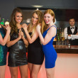 Sexy friends posing in front of barkeeper — Stockfoto