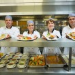 Four young chefs showing plates — Stock Photo