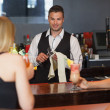 Handsome bartender working while gorgeous friends speaking — Stock Photo