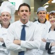 Restaurant manager standing in front of team of chefs — Stock Photo