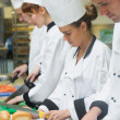 Stock Photo: Chefs standing in a row cutting vegetables