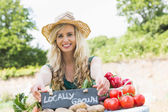 Happy young female farmer standing at her stall — Stock Photo