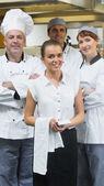 Waitress standing in front of team of chefs — Foto Stock