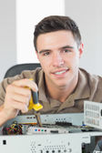 Handsome happy computer engineer repairing open computer — Stock Photo