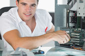 Smiling computer engineer repairing computer with pliers — Stock Photo