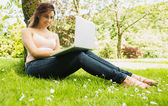 Happy young woman leaning against a tree while using her notebook — Stock Photo