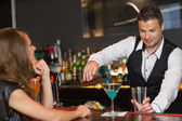 Handsome bartender serving cocktail to attractive woman — Stock Photo