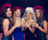 Laughing friends clinking champagne glasses at a hen night — Stock Photo