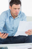 Worried casual man holding calculator paying bills looking at document — Stock Photo