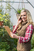 Phoning woman holding a clipboard in her green house — Stockfoto