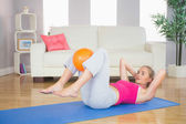 Sporty calm blonde doing sit ups holding ball between knees — Stock Photo