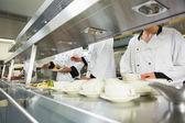 Quatro chefes a trabalhar em uma cozinha — Fotografia Stock