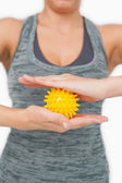 Close up of young woman holding yellow massage ball between her hands — Stock Photo