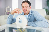 Good looking casual man putting coin in piggy bank and looking down — Stockfoto