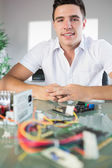Attractive computer engineer sitting at desk looking at camera — Stock Photo
