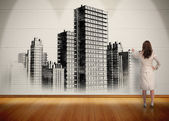 Businesswoman painting black and white city on wall — Stock Photo