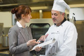 Young female manager talking to the head cook — Stock Photo