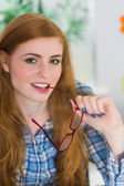 Smiling redhead biting her reading glasses — Stok fotoğraf