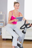 Sporty smiling blonde training on exercise bike using tablet — Stock Photo