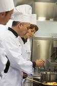 Head chef inspecting his students pot — Stock Photo