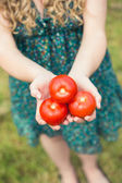 Blonde woman holding some tomatoes — Stock fotografie