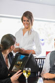 Businesswoman ordering dinner from pretty waitress — Stock Photo