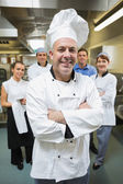 Head chef posing with his team behind him — Stock Photo