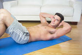 Smiling handsome man doing sit ups — Stock Photo