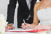 Close up of young bride signing wedding contract — Stock Photo