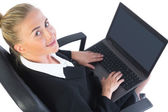 Cute businesswoman using her notebook sitting on an office chair — Foto Stock