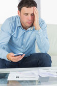 Worried casual man holding calculator paying bills — Stock Photo