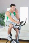 Stern handsome man training on exercise bike phoning — Stock Photo