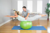 Physiotherapist helping patient doing exercise with exercise ball — Stock Photo