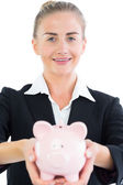 Pretty businesswoman holding pink piggy bank — Stockfoto