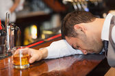 Drunk businessman lying on a counter — Stock Photo