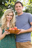 Young couple holding a bowl with apples — Stockfoto