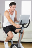 Sporty man with earphones exercising on bike looking at laptop — Stockfoto
