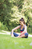 Young fit woman sitting on the ground — ストック写真