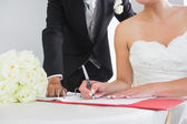 Mid section of a young couple signing wedding contract — Stock Photo