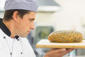 Young baker inspecting a seeded loaf of bread — Stock Photo