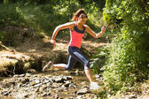 Sporty young woman leaping over a stream — Stock Photo