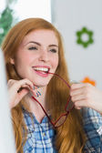 Beautiful redhead sitting at her desk and biting her glasses — Stok fotoğraf