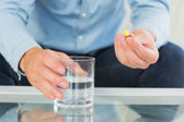 Close up of man holding glass of water and pill — Stock Photo