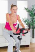 Sportowa wesoła blondynka szkolenia na rower treningowy — Fotografia Stock