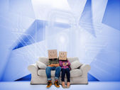 Couple with cartons on head sitting on couch under white holographic lock — Stock Photo