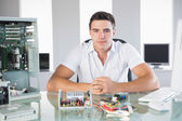 Handsome computer engineer sitting at desk looking at camera — Stock Photo
