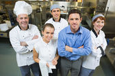 Handsome manager posing with some chefs and waitress — Stock Photo